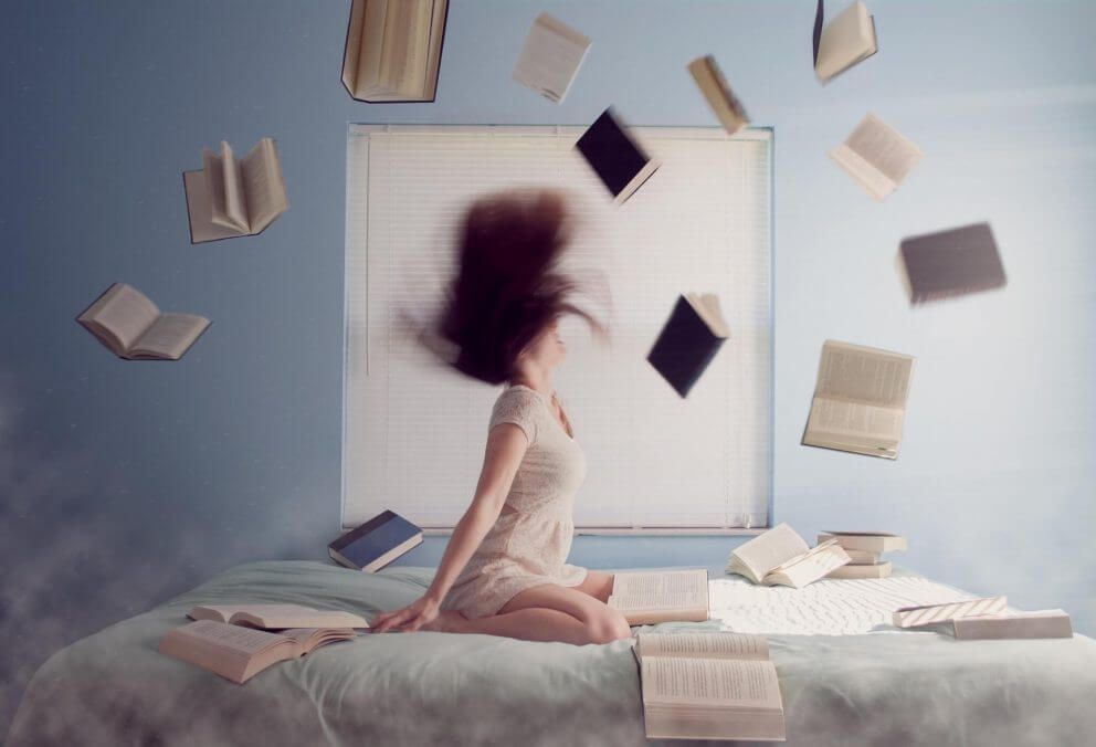 A girl sits on her bed as books fly around the room