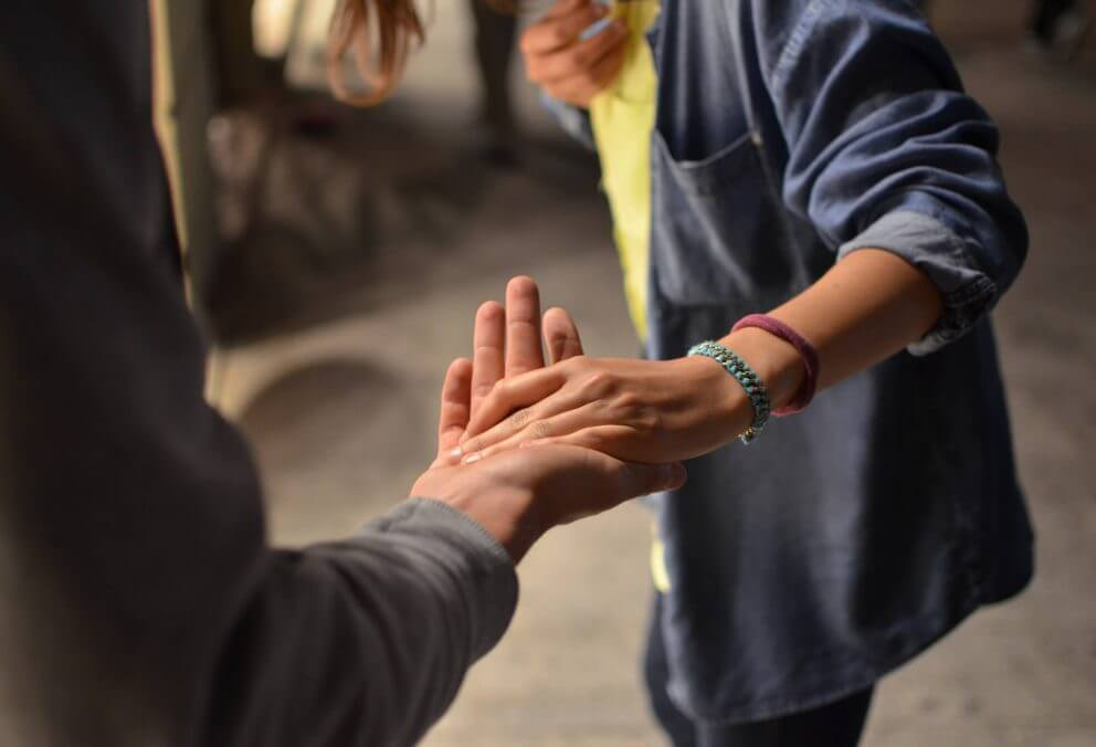 2 people reaching out and holding hands
